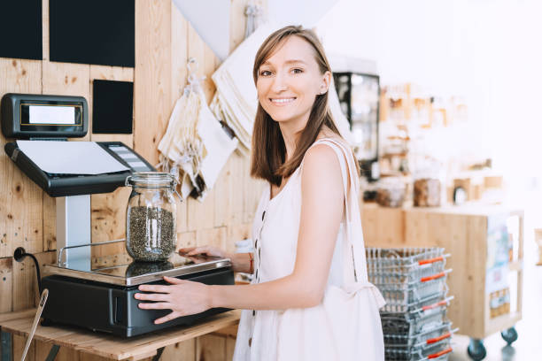 Girl weighs glass jar with hemp seeds. Woman with cotton bag chooses and buys products in zero waste shop. stock photo