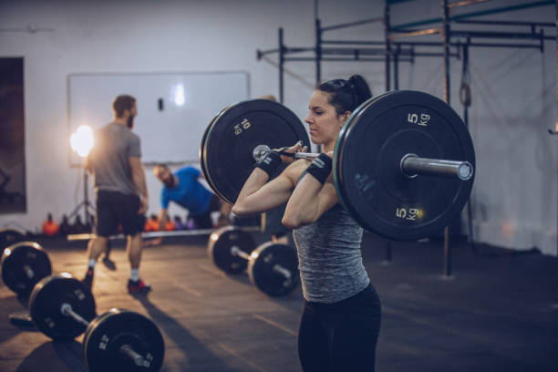 Girl weightlifting in gym stock photo