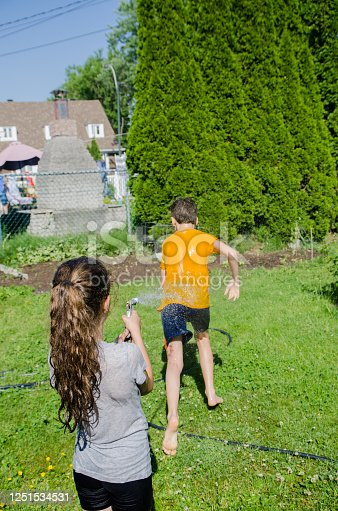 585604690 istock photo Girl wetting her brother while he's running away 1251534531