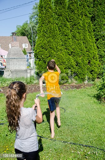 585604690 istock photo Girl wetting her brother while he's running away 1251534800