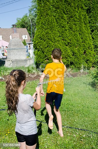 585604690 istock photo Girl wetting her brother while he's running away 1251537483