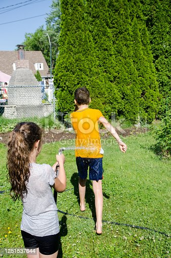 585604690 istock photo Girl wetting her brother while he's running away 1251537644