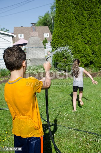 585604690 istock photo Girl wetting her brother while he's running away 1251538518