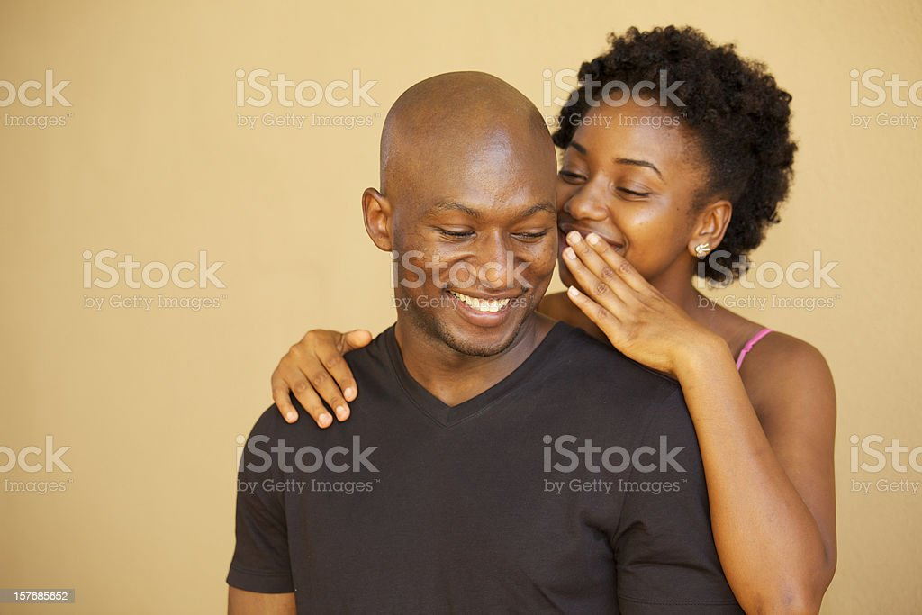 Girl whispering in a guy's ear royalty-free stock photo
