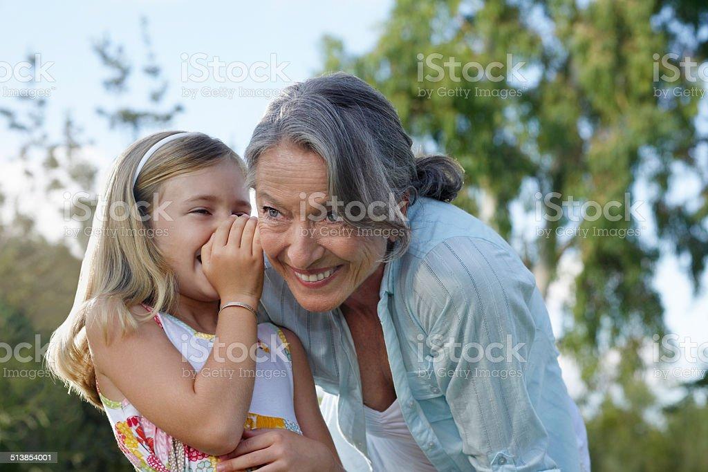 Girl cuchicheaban en abuela de la oreja - foto de stock