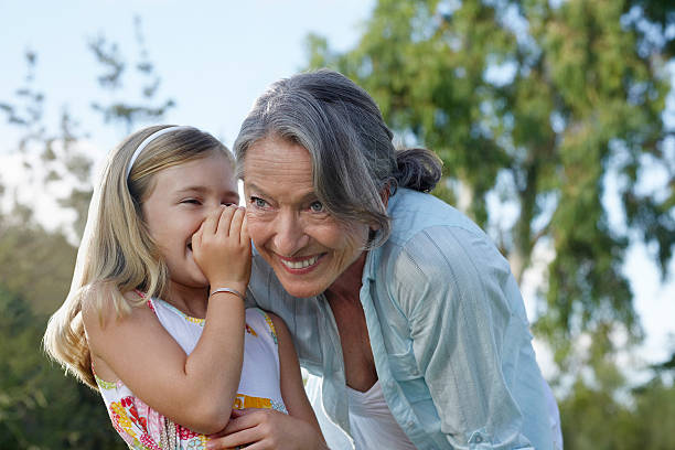 girl whispering in grandmother's ear - granddaughter and grandmother stock photos and pictures