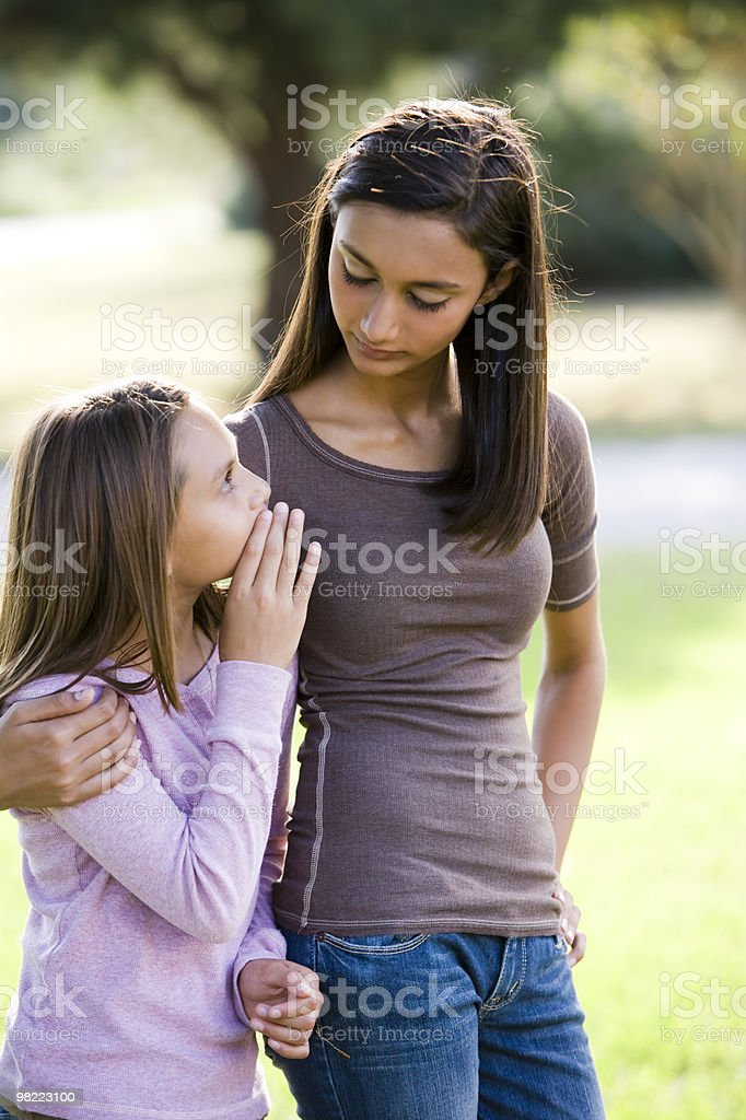 Girl whispering to her older teenage sister royalty-free stock photo