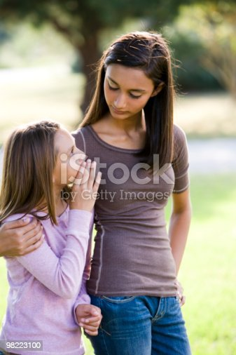 Girl Whispering To Her Older Teenage Sister Stock Photo & More Pictures of 10-11 Years