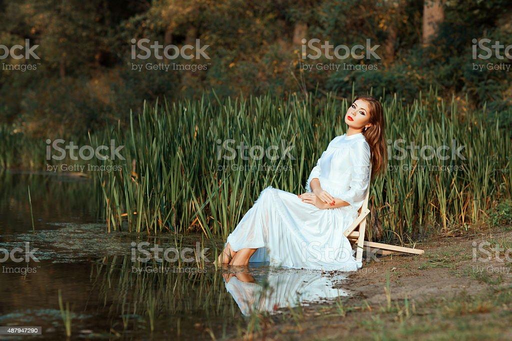 Girl white dress sitting dipping feet in the lake. stock photo