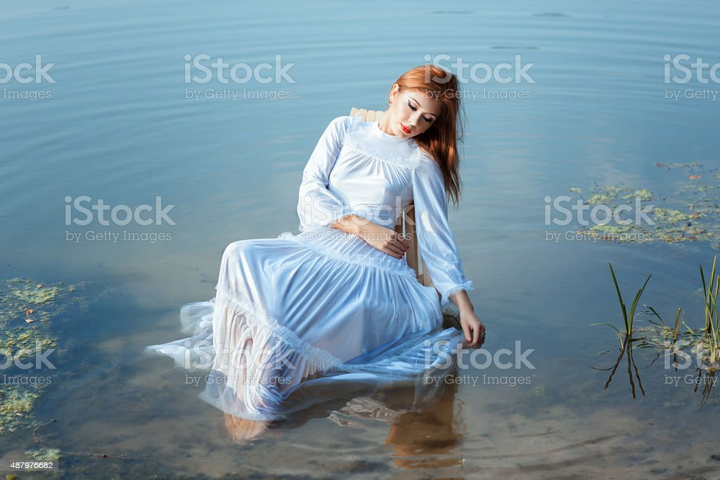 Girl white dress sitting on chair in a lake. stock photo