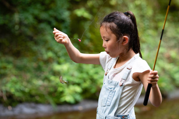 Girl who caught a small fish stock photo
