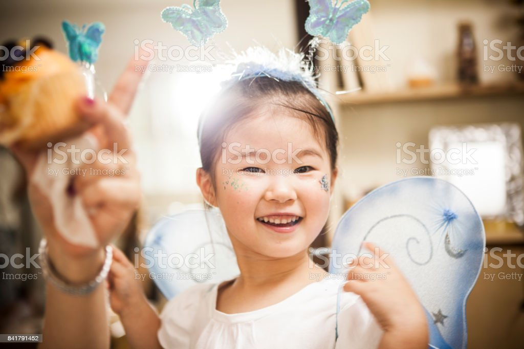 A girl who costumes a fairy is playing with a magic wand. stock photo