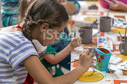 istock Girl who paints a ceramic bowl 540568262