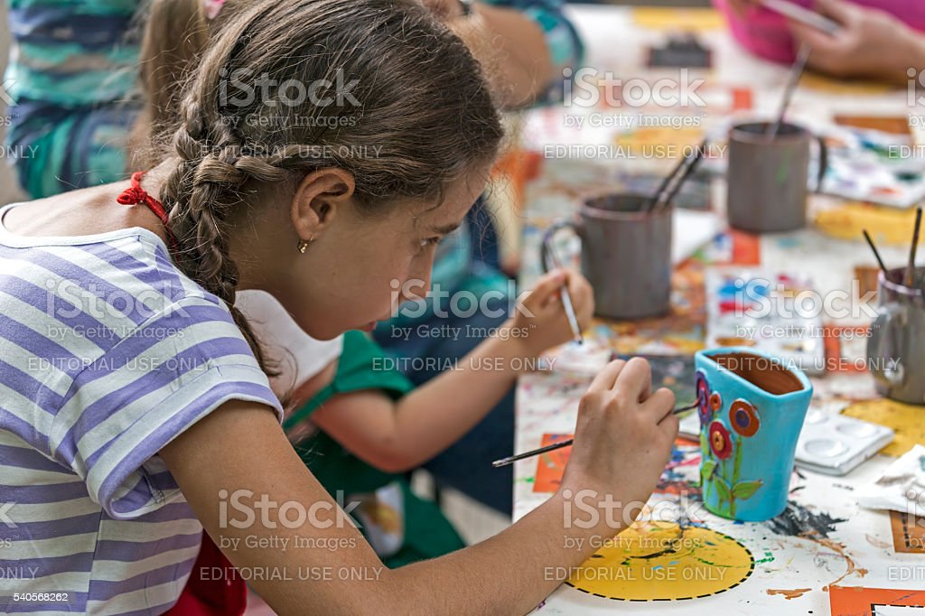 Girl who paints a ceramic bowl stock photo