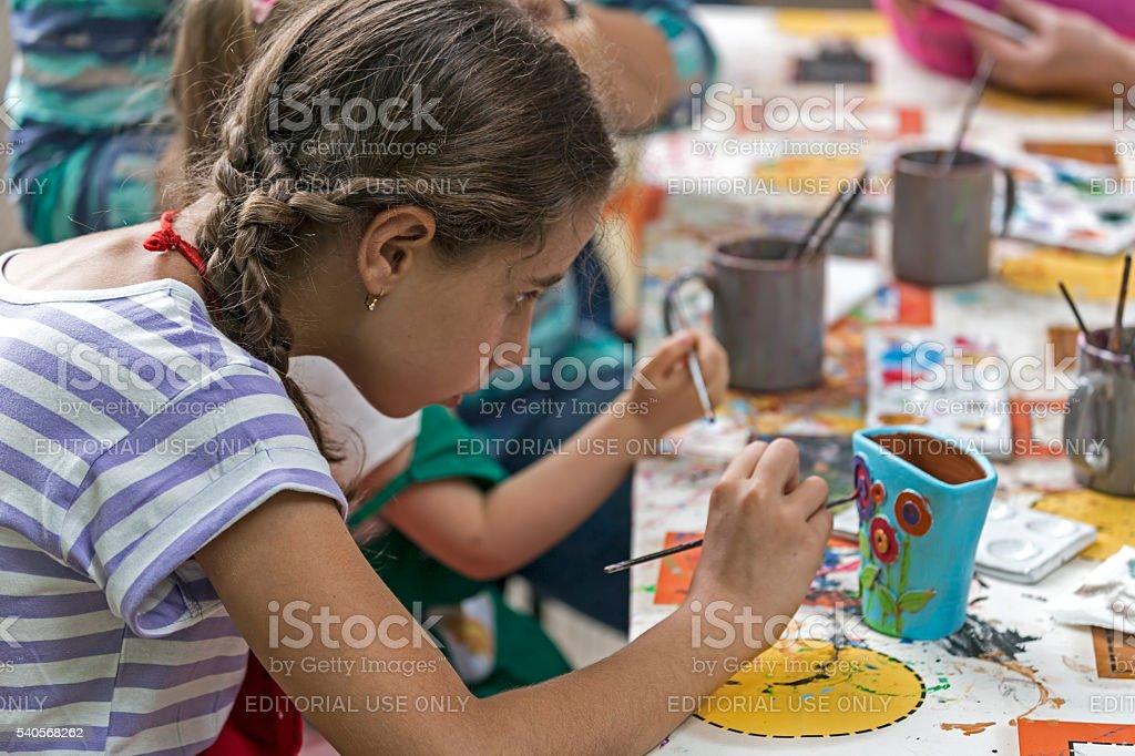 Garota que pinta um prato de cerâmica - foto de acervo