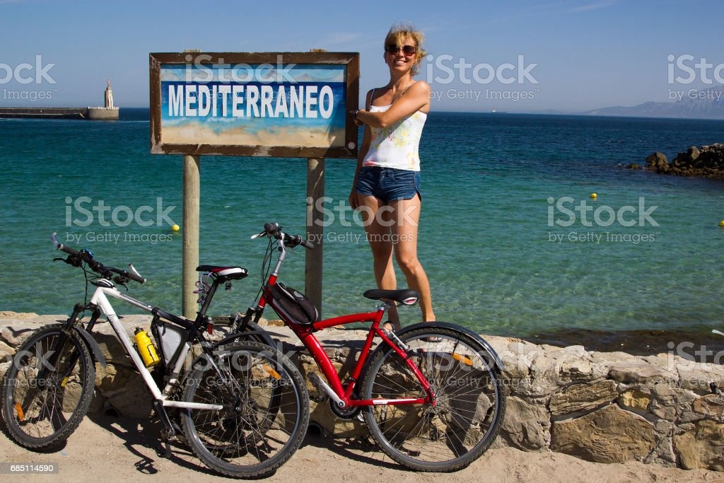 Girl with 2 bicycles against Mediterraneo sign at seaside Spain royalty-free stock photo