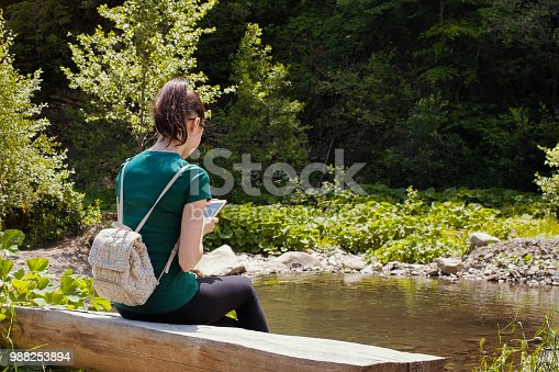 istock Girl with a backpack and a smartphone sitting on a river bank. Summer sunny day 988253894