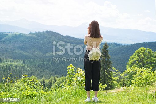 istock Girl with a backpack on a smartphone photographs of mountains and forest. Back view. Sunny summer day 988253852