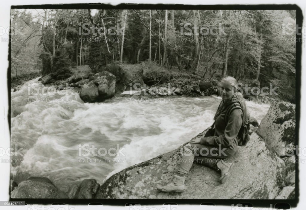 A girl with a backpack on her back sits on the river bank.