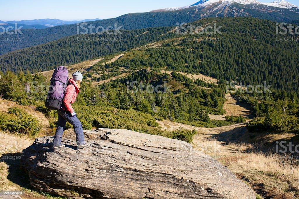 Chica con una mochila de pie sobre roca. foto de stock libre de derechos