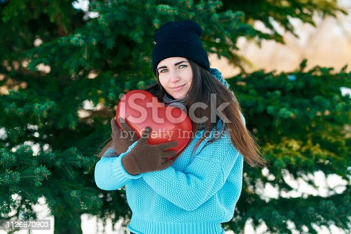 attractive young girl with a balloon in the shape of a heart in hands. Valentine's Day