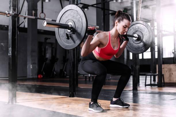 重量挙げのジムでバー ベルを持つ少女 - ウエイトトレーニング ストックフォトと画像