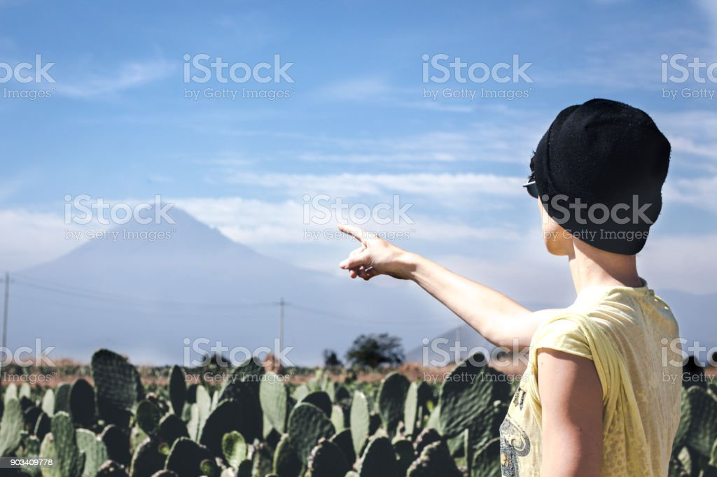 Girl with a beani pointing to a volcano from a field of nopales stock photo