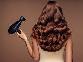 Girl with a beautiful hairstyle holding a hairdryer