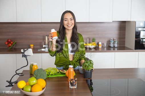 Cute young female blogger holding a sealed vitamin bottle in her hand