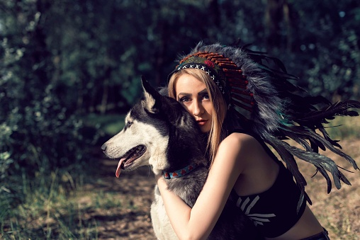 A girl with a dog in an Indian headdress