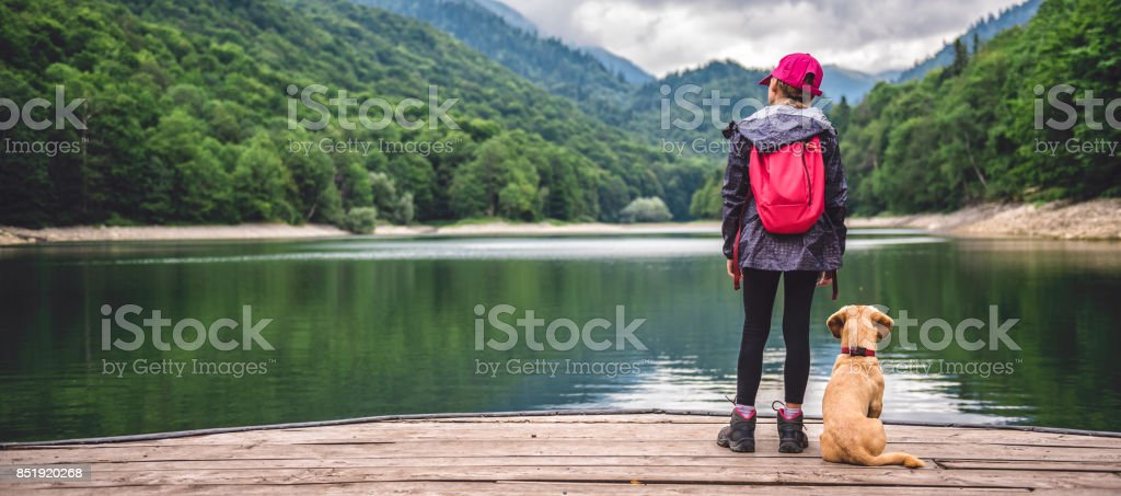 Girl with a dog standing on pier by the lake stock photo