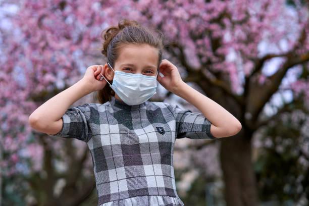 chica con una máscara facial está en la ciudad al aire libre, árboles en flor, temporada de primavera, tiempo de floración - concepto de alergias y protección de la salud contra el aire polvoriento - foto de stock