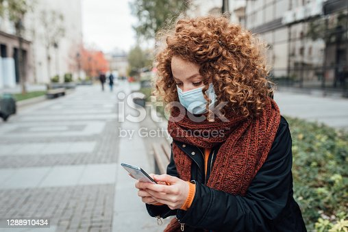 Beautiful young woman taking a break in the city after shopping and using her smartphone.