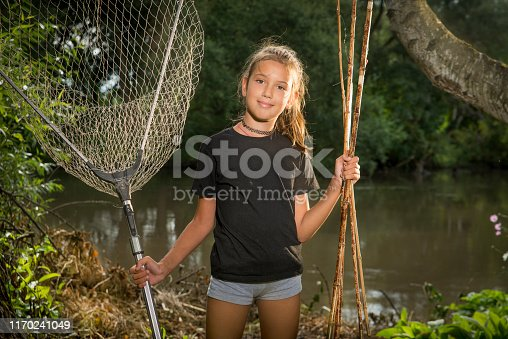 Girl with a fishing rod and a bucket for fish on the river Bank.