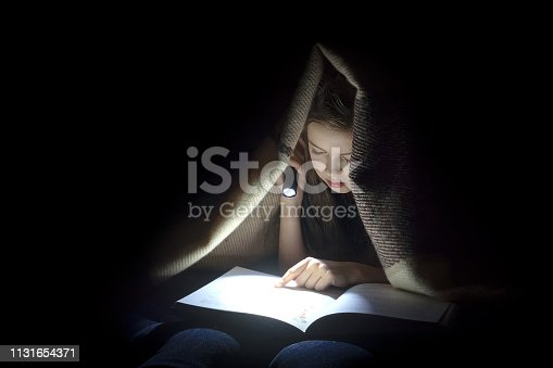 Girl with a flashlight reading a book.