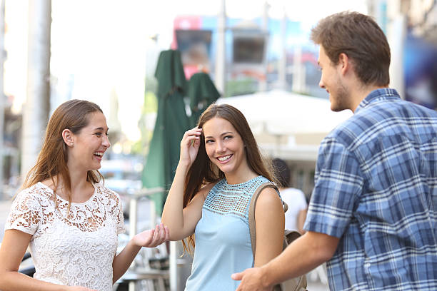 Girl with a friend flirting with a boy Candid girl with a friend flirting with a boy in the street stranger stock pictures, royalty-free photos & images
