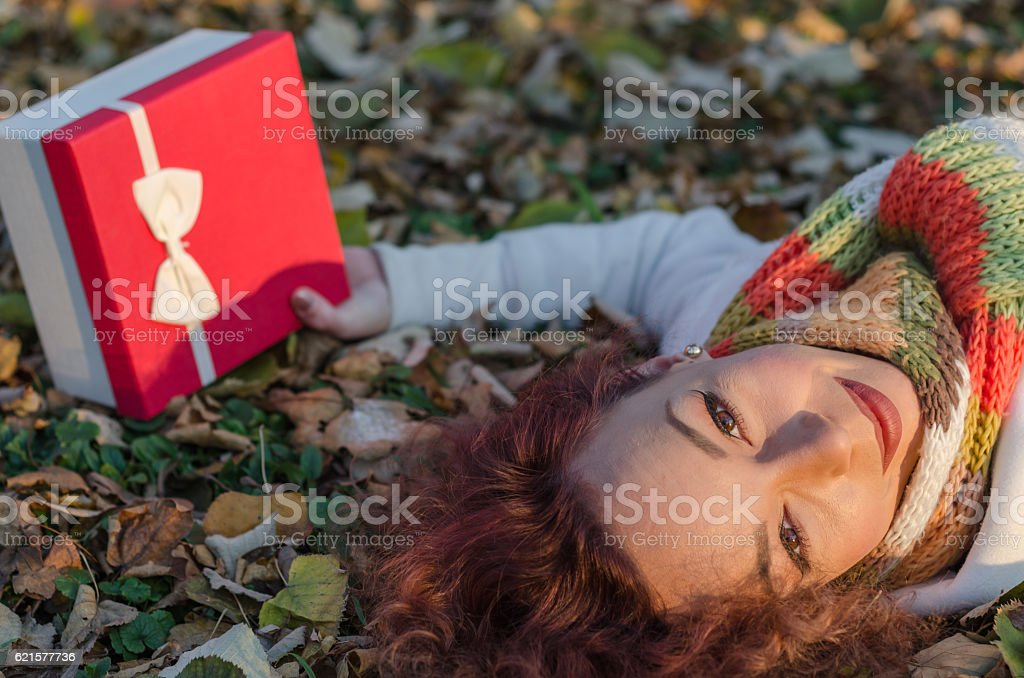 Girl with a gift in hand lying on the leaves photo libre de droits