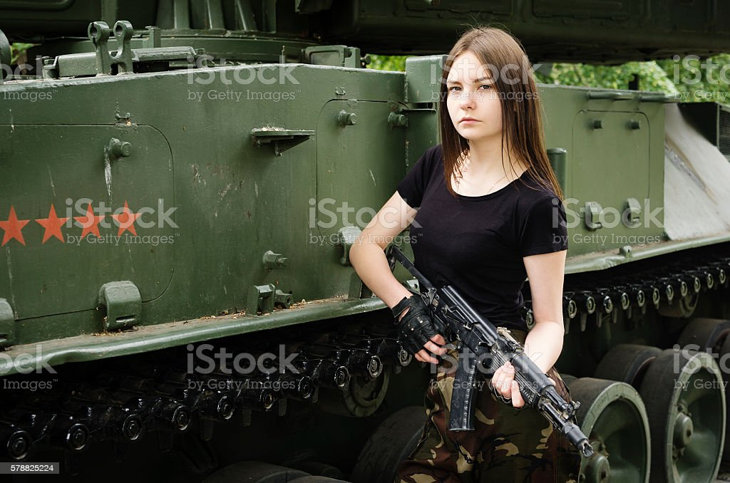Girl with a gun near the armored vehicles stock photo