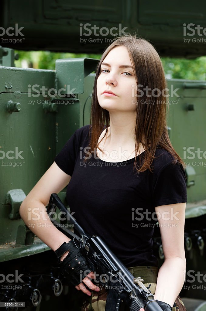 Girl with a gun standing near the armored cars stock photo
