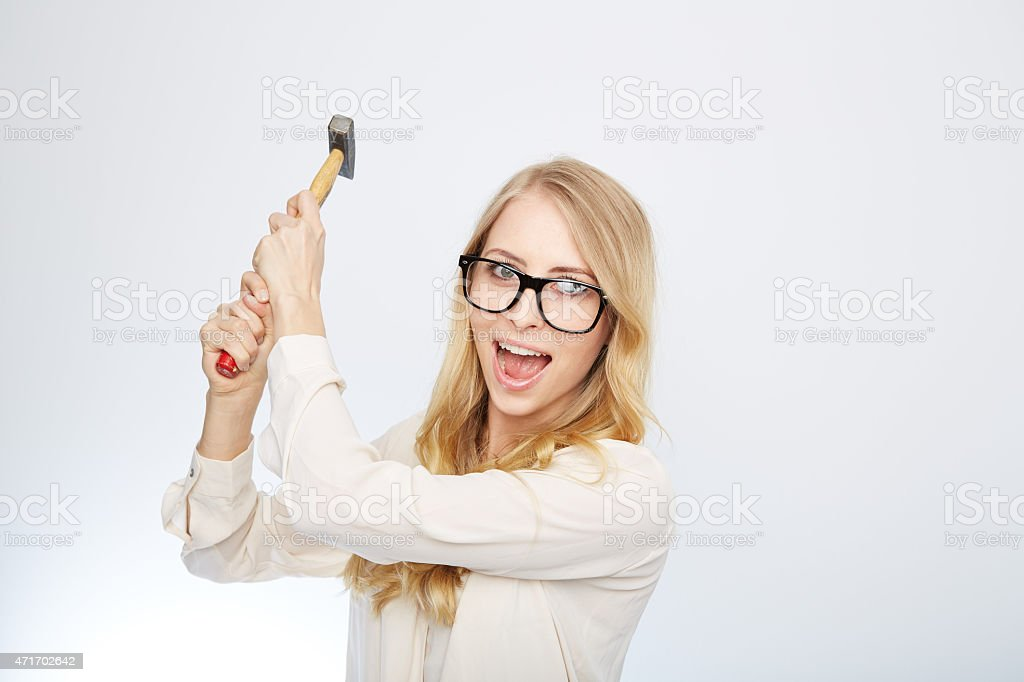 girl with a hammer and nerd glasses. isolated on white stock photo