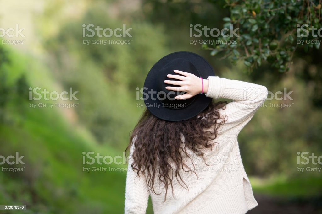 A girl with a hat on a trail stock photo