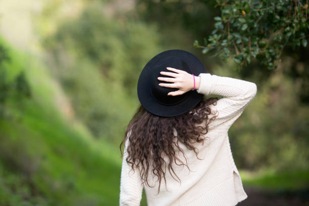 A girl with a hat on a trail a girl holding her hat on jude beck stock pictures, royalty-free photos & images