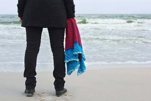 Girl with a knitted shawl on sea beach