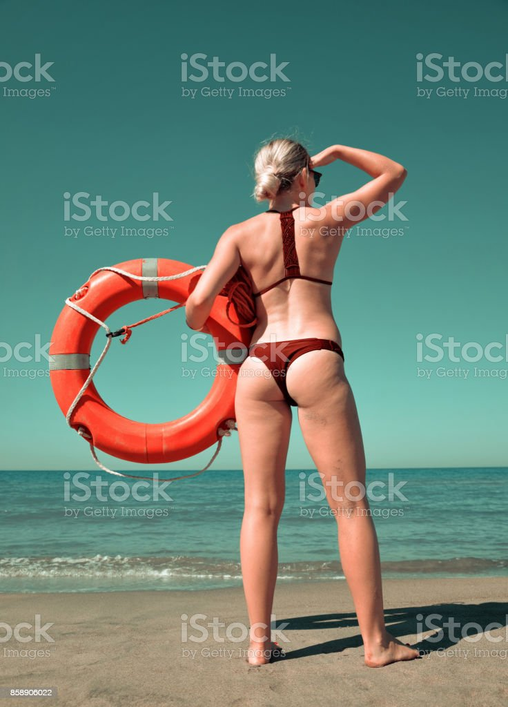 Girl with a lifebuoy on the beach. stock photo