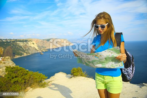 istock girl with a map on the beautiful coast 483320583