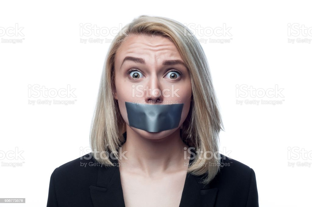 Girl with a mouth taped on a white background stock photo