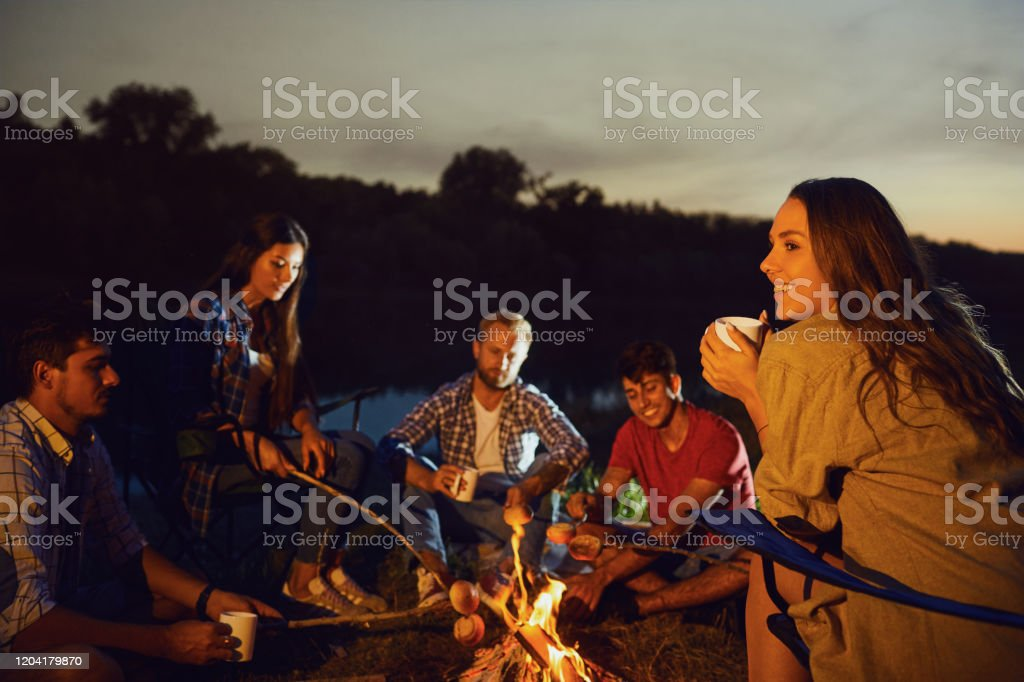 Girl With A Mug Of Tea Against The Backdrop Of Friends By The Bonfire At Night Stock Photo Download Image Now Istock