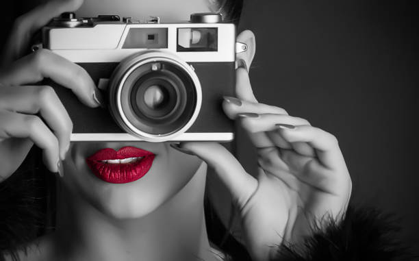Girl with a retro camera A beautiful girl with a retro camera, a black and white photo with red lips image stock pictures, royalty-free photos & images