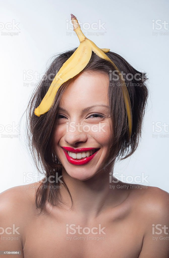 Girl with a skin of a banana on his head stock photo