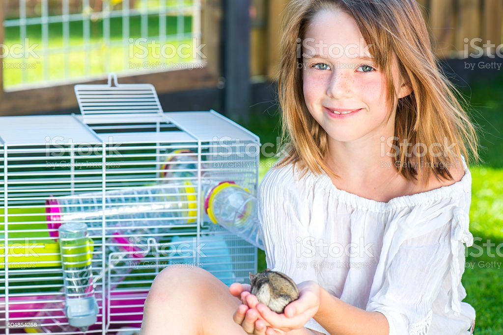 Girl with a small hamster in palms stock photo